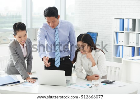 Asian business people discussing information on laptop screen