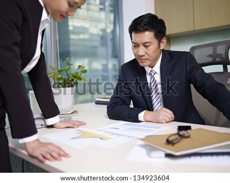 asian business people reviewing sales performance in office. - stock photo