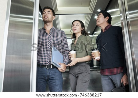 people inside elevator. asian business people with take-out coffee in elevator inside e