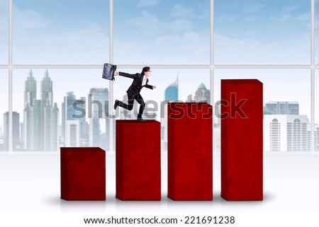 Asian business person runs hurry above business graph - stock photo