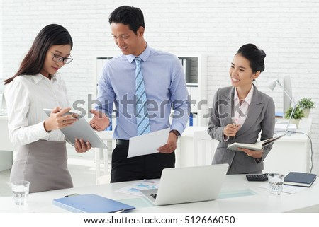 Asian business team discussing idea on tablet computer