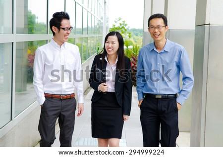 Asian business team having conversation while walking - stock photo