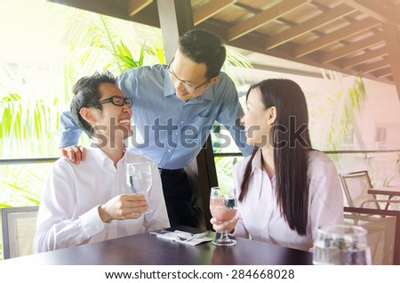 Asian business team having discussion in the restaurant - stock photo