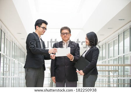 asian business team in a reporting meeting with office background