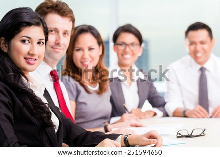 Asian Business Team in conference meeting looking at camera