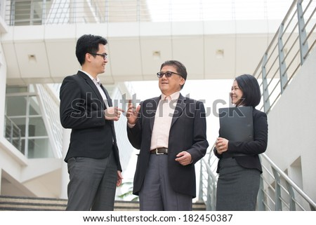 asian business team in conversation with office background