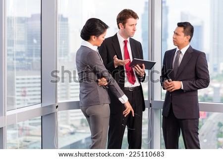 Asian business team in front of urban skyline