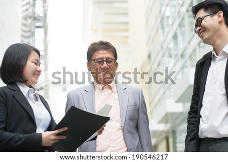 Asian business team meeting. Business executive presenting charts to CEO boss over office.