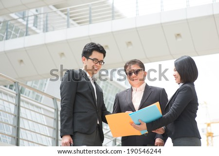 Asian business team meeting, showing report to CEO and having discussion. Modern office background. - stock photo