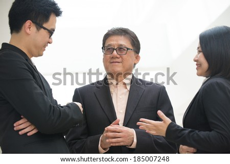 asian business team meeting with senior ceo with office background - stock photo