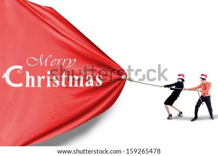 Asian business team pull christmas banner - stock photo