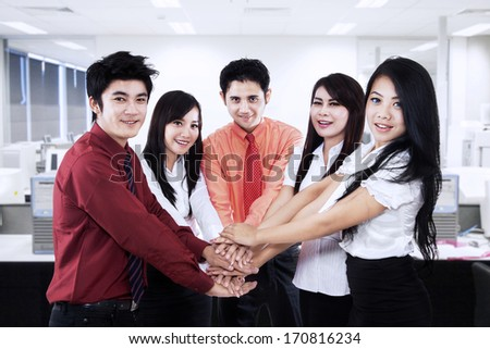 Asian business team showing unity by joining their hands together - stock photo