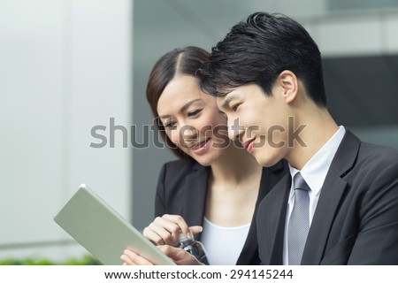 Asian business woman and man talk a pad and talk. - stock photo