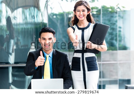 Asian business woman and man working outside on computer