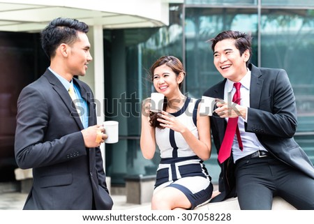 Asian business woman and men having coffee break outside in front of building  - stock photo