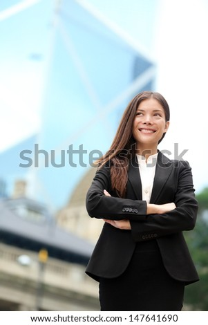 Asian business woman confident outdoor in Hong Kong standing proud in suit cross-armed in business district. Young mixed race female Chinese Asian / Caucasian female professional in central Hong Kong. - stock photo