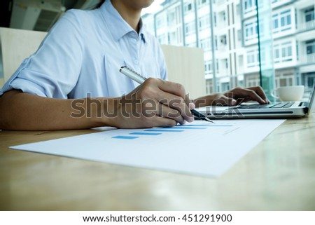 Asian business woman discussing data with computer and calculating on charts. Business concept.   - stock photo