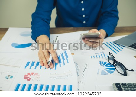 asian business woman hand pointing graph discussion and analysis data charts and graphs and using smart phone with social network working at home office.Business finances and accounting concept