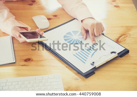 Asian business woman hand working on laptop computer with digital layer business graph information diagram on wooden desk as concept vintage tone - stock photo