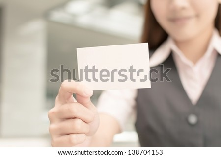 Asian business woman hold a blank business card, closeup portrait in outside of modern city.