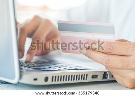 Asian business woman holding a credit card and using laptop for online shopping.(selective focus)