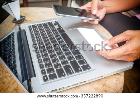 Asian business woman holding a credit card and using laptop for online shopping.vintage tone Retro filter effect,soft focus,low light.(selective focus)
