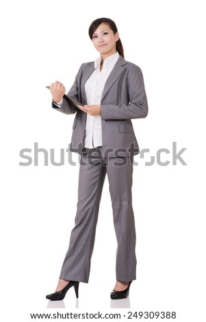 Asian business woman holding pad, full length portrait on white background. - stock photo