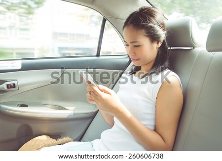 asian business woman in a taxi. she is watching something on her smart phone - stock photo