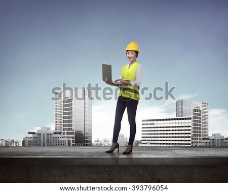 Asian business woman in safety vest standing on the building rooftop while holding laptop - stock photo