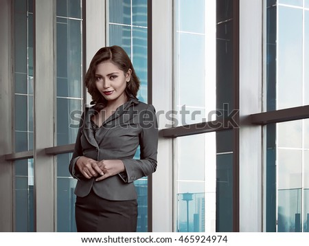 Asian business woman in the office wearing a gray suit, appear tempting and attractive