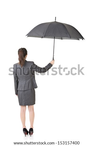 Asian business woman is holding umbrella. Full length portrait. Rear view. Isolated on the white background. - stock photo