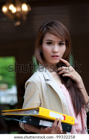 asian business woman is holding yellow and black business files - stock photo