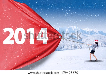 Asian business woman is pulling new year 2014 - stock photo