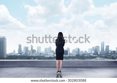 Asian business woman looking to the city from rooftop building - stock photo