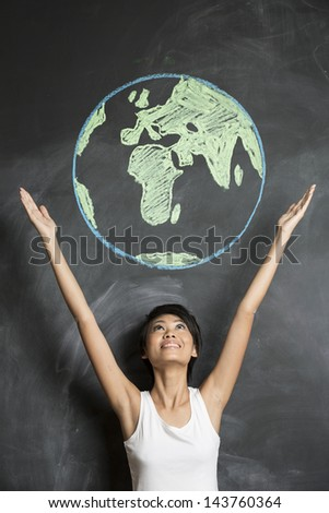 Asian Business woman or teacher with chalk globe drawn on blackboard. - stock photo