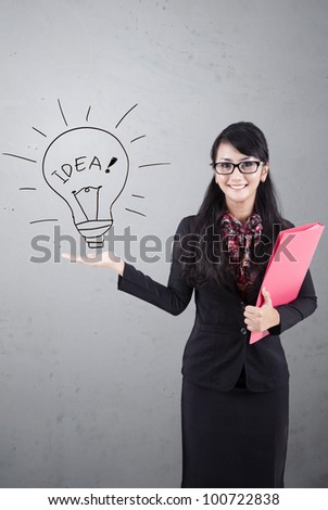 Asian business woman presenting idea. Shot over white board - stock photo