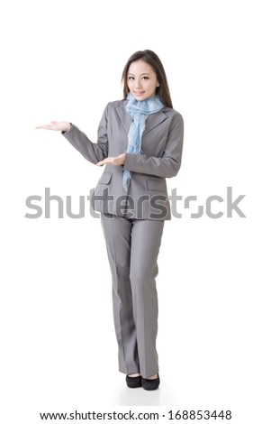 Asian business woman showing and introducing, full length portrait isolated on white background. - stock photo