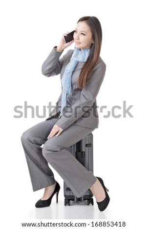 Asian business woman sit with a suitcase, full length portrait isolated on white background. - stock photo
