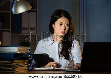 asian business woman touch screen on digital tablet working overtime late night. indoors office background