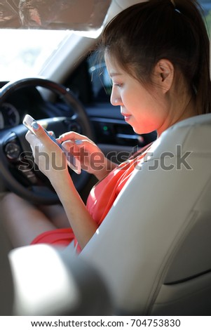 asian business woman using mobile phone communication working in vehicle car