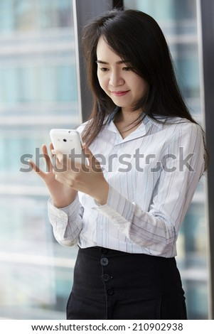 Asian business woman using smart phone in the office. - stock photo