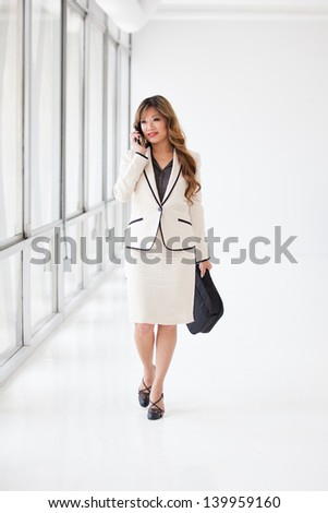Asian Business Woman walking while on her cell phone   at the Airport - stock photo