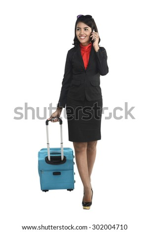 Asian business woman with cellphone and suitcase isolated over white background - stock photo