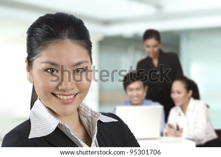 Asian business woman with her team in background. - stock photo