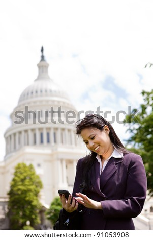 Asian business woman with smartphone on Capitol Hill in Washington DC - stock photo