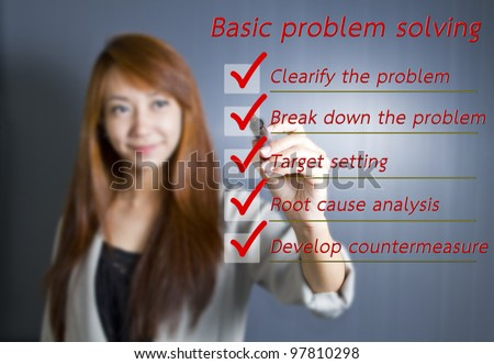Asian business woman writing Basic problem solving on whiteboard