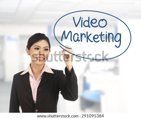 Asian business woman writing video marketing on office background