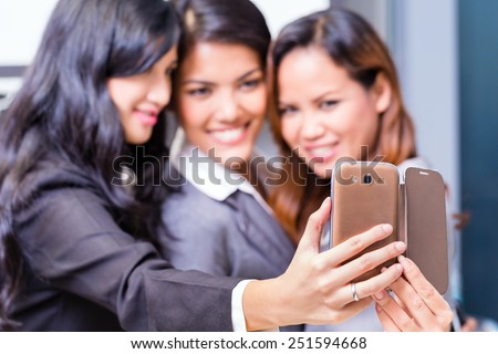 Asian Business women taking selfie with smart phone - stock photo