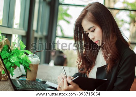 Asian business women working and writing a book ,soft focus and blurry  - stock photo