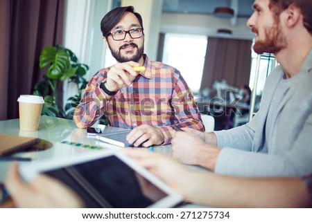 Asian businessman answering questions of his colleagues - stock photo